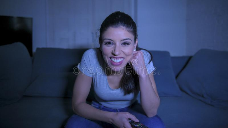 Young beautiful and happy latin woman on her 30s holding TV remote enjoying at home living room couch watching television show stock photos