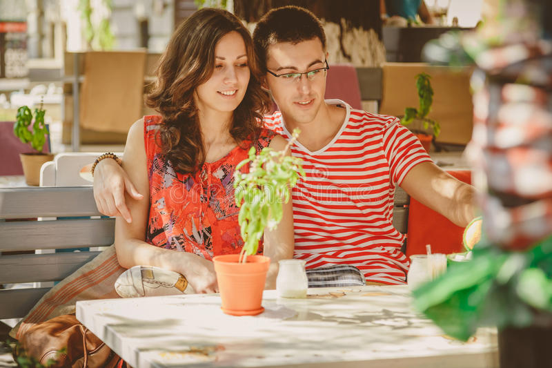Young beautiful happy loving couple sitting at street open-air cafe, hugging. Beginning of love story. Relationship love royalty free stock photo
