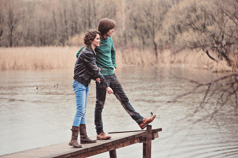 Young beautiful happy loving couple on the walk in early spring. On river side royalty free stock photography