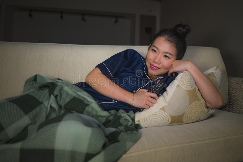 Young beautiful happy and relaxed Asian Korean woman at home living room sitting cozy on sofa couch watching TV show episode or royalty free stock photos