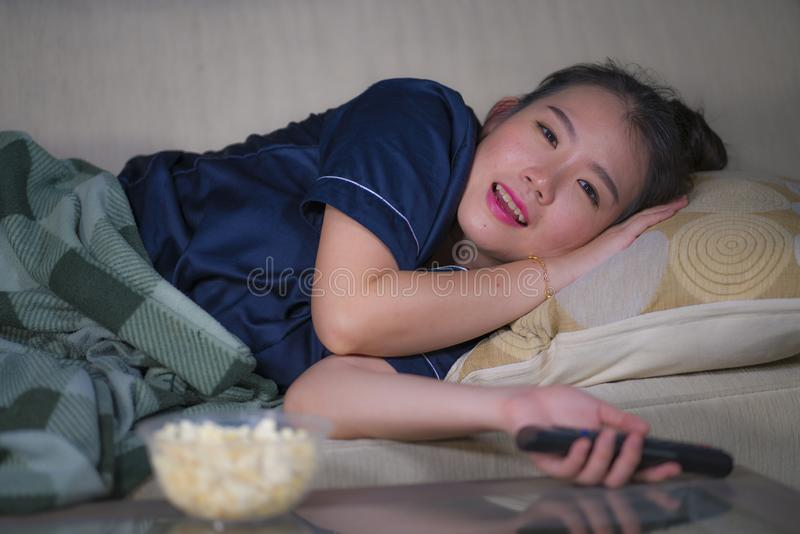 Young beautiful happy and relaxed Asian Chinese woman at home living room lying cozy on sofa couch watching TV show episode or royalty free stock image