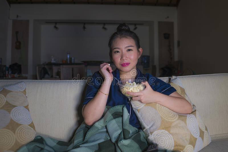 Young beautiful happy and relaxed Asian Chinese woman at home living room sitting cozy on sofa couch watching TV show episode or stock images