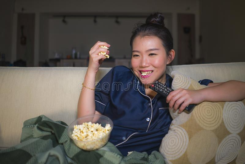 Young beautiful happy and relaxed Asian Chinese woman at home living room sitting cozy on sofa couch watching TV show episode or stock image