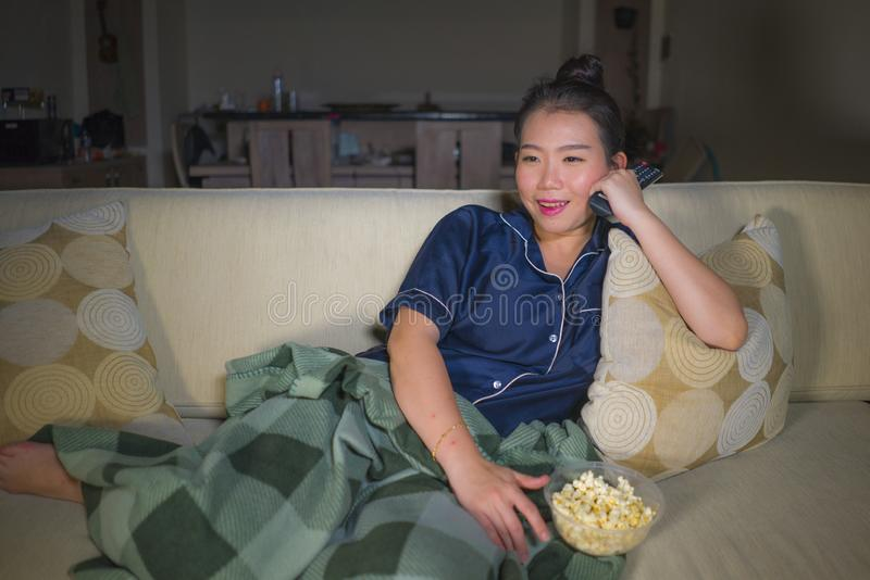 Young beautiful happy and relaxed Asian Chinese woman at home living room sitting cozy on sofa couch watching TV show episode or royalty free stock photo