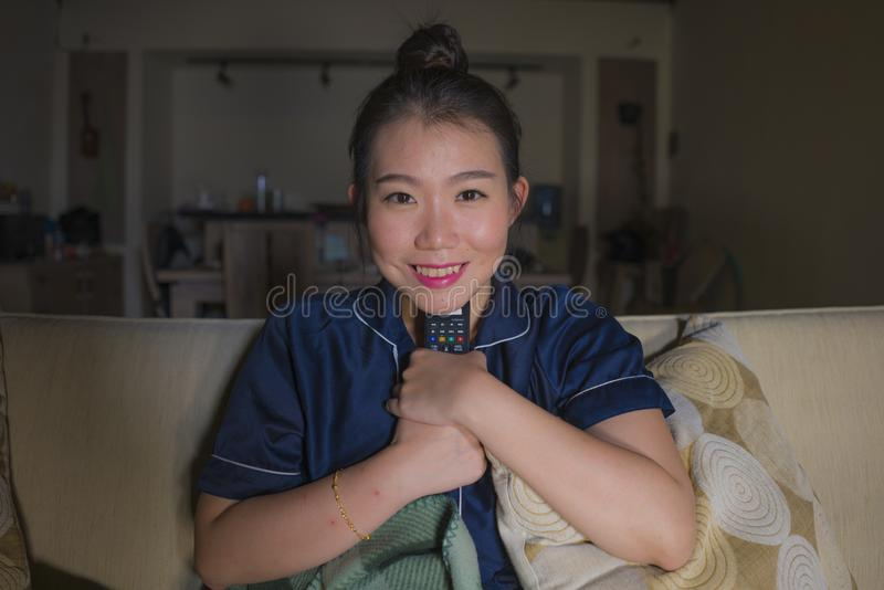 Young beautiful happy and relaxed Asian Chinese woman at home living room sitting cozy on sofa couch watching TV show episode or royalty free stock photos