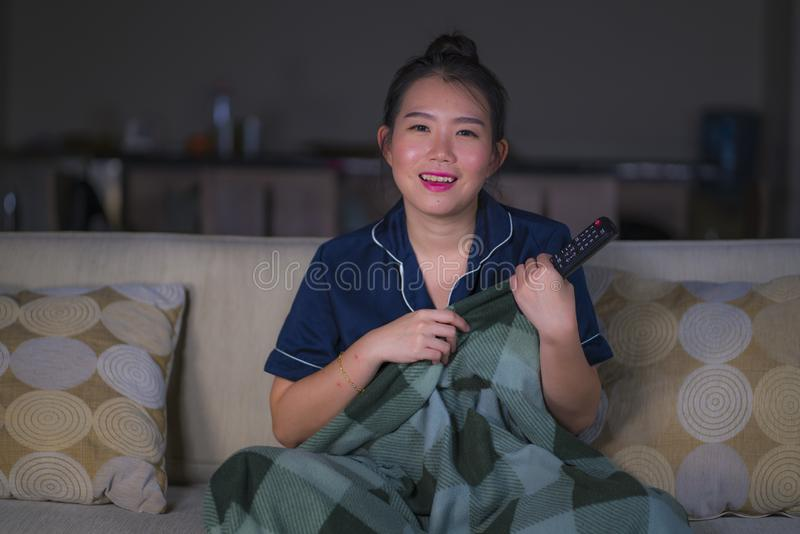 Young beautiful happy and relaxed Asian Chinese woman at home living room sitting cozy on sofa couch watching TV show episode or royalty free stock images