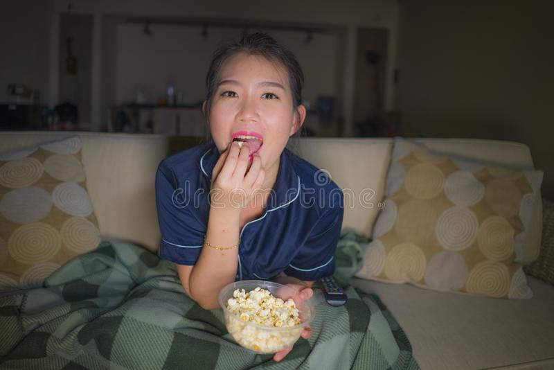 Young beautiful happy and relaxed Asian Japanese woman at home living room sitting cozy on sofa couch watching TV show episode or. Romantic comedy movie eating royalty free stock image