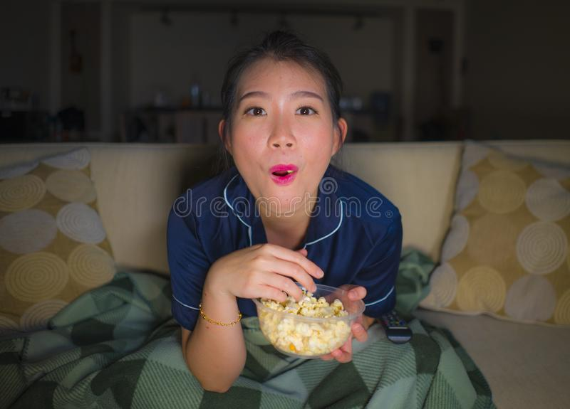 Young beautiful happy and relaxed Asian Japanese woman at home living room sitting cozy on sofa couch watching TV show episode or. Romantic comedy movie eating royalty free stock photography