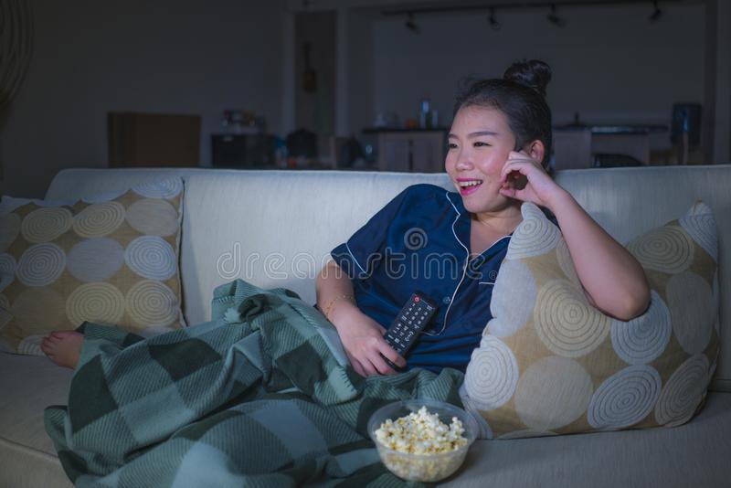 Young beautiful happy and relaxed Asian Japanese woman at home living room sitting cozy on sofa couch watching TV show episode or. Romantic comedy movie eating stock photo