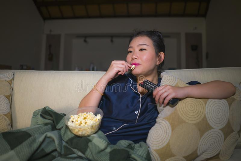 Young beautiful happy and relaxed Asian Japanese woman at home living room sitting cozy on sofa couch watching TV show episode or. Romantic comedy movie eating royalty free stock photo