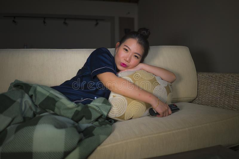 Young beautiful happy and relaxed Asian Japanese woman at home living room sitting cozy on sofa couch watching TV show episode or. Young beautiful happy and royalty free stock photo