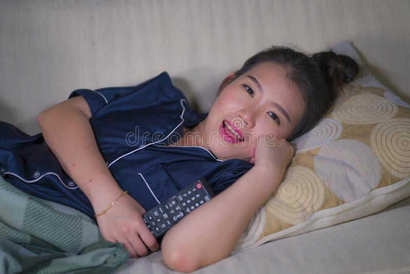 Young beautiful happy and relaxed Asian Japanese woman at home living room sitting cozy on sofa couch watching TV show episode or. Young beautiful happy and stock photo