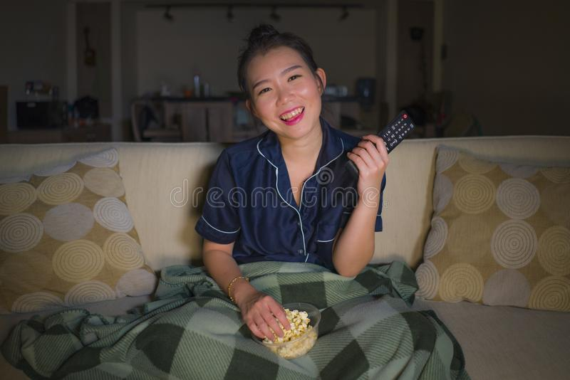 Young beautiful happy and relaxed Asian Japanese woman at home living room sitting cozy on sofa couch watching TV show episode or. Romantic comedy movie smiling stock photography