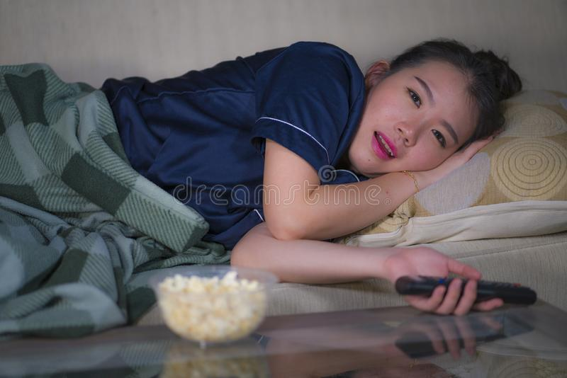 Young beautiful happy and relaxed Asian Korean woman at home living room lying cozy on sofa couch watching TV show episode or stock photography