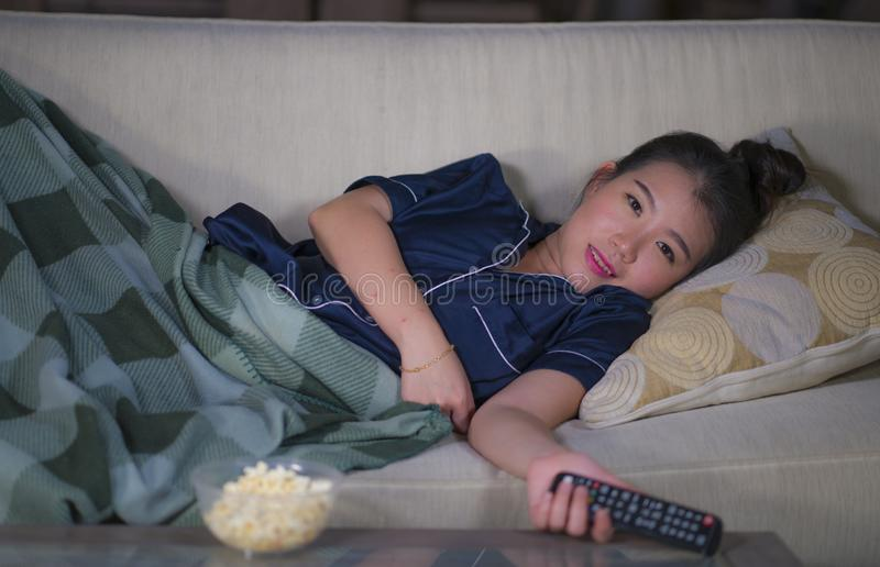 Young beautiful happy and relaxed Asian Korean woman at home living room lying cozy on sofa couch watching TV show episode or royalty free stock image