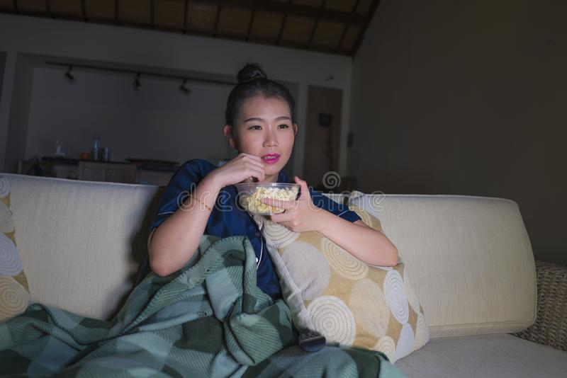 Young beautiful happy and relaxed Asian Korean woman at home living room sitting cozy on sofa couch watching TV show episode or. Romantic comedy movie eating royalty free stock photography