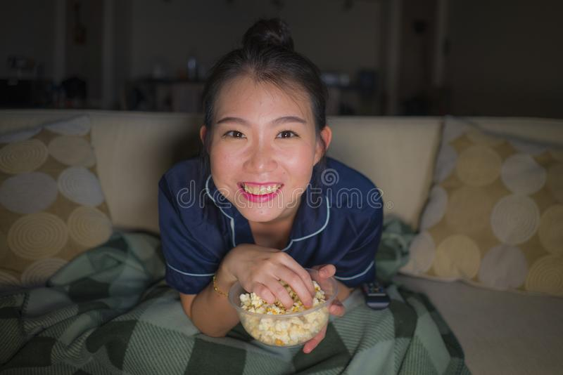 Young beautiful happy and relaxed Asian Korean woman at home living room sitting cozy on sofa couch watching TV show episode or stock photos