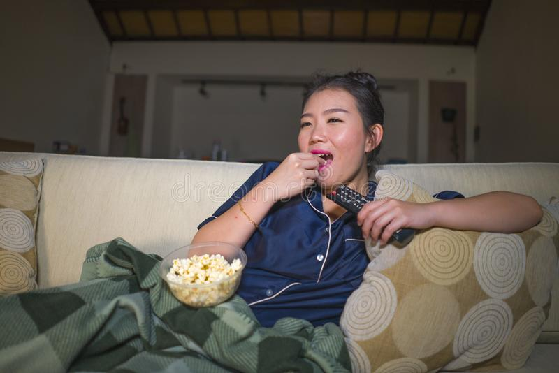 Young beautiful happy and relaxed Asian Korean woman at home living room sitting cozy on sofa couch watching TV show episode or stock images