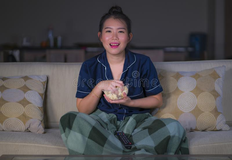 Young beautiful happy and relaxed Asian Korean woman at home living room sitting cozy on sofa couch watching TV show episode or stock photography