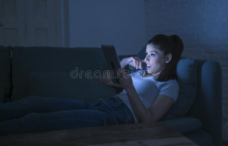 Young beautiful happy and relaxed latin woman 30s lying on home couch late night using digital device laptop tablet pad watching stock image