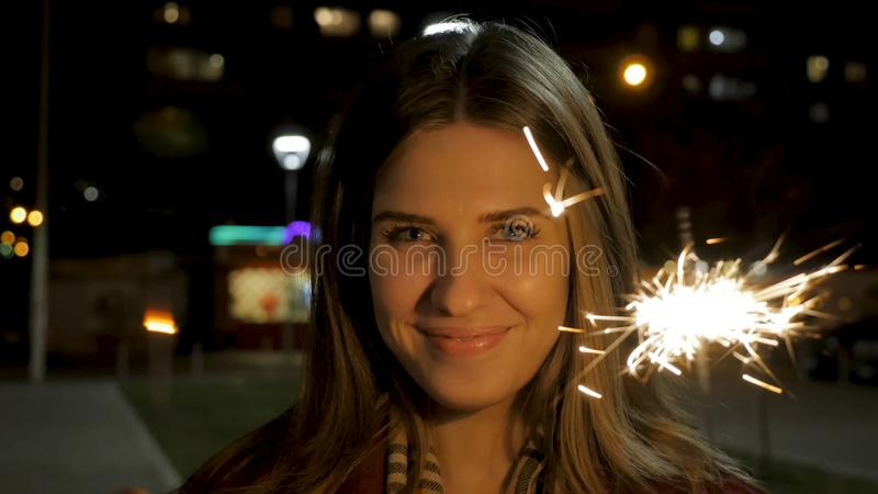 Young beautiful happy smiling girl holding sparkler on the street. Holiday concept. Girl with sparklers in the street stock photo