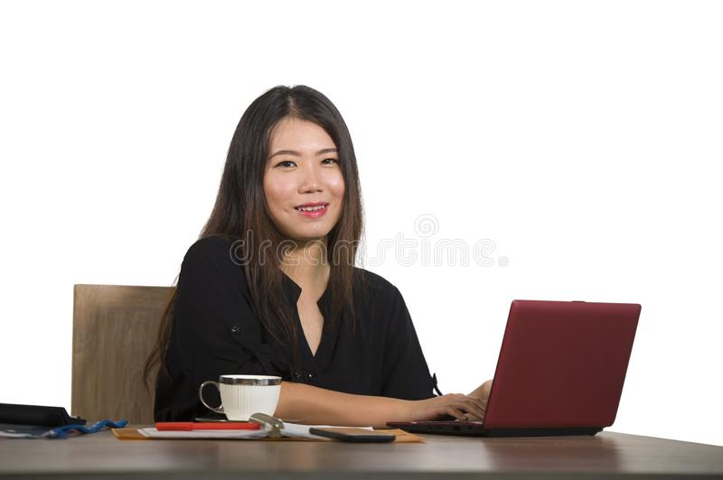 Young beautiful and happy successful Asian Korean businesswoman working relaxed at office computer desk smiling confident posing c royalty free stock photos