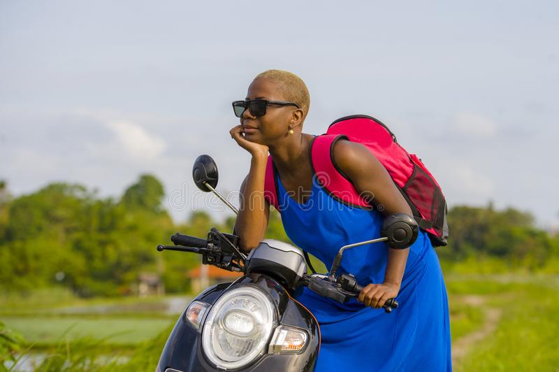 Young beautiful and happy tourist african american black woman l. Ooking around with scooter motorbike at green field tropical landscape in adventure trip and stock photography