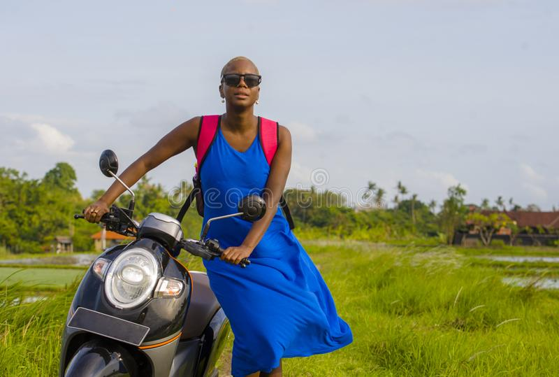 Young beautiful and happy tourist african american black woman looking around with scooter motorbike at green field tropical lands. Cape in adventure trip and stock photos