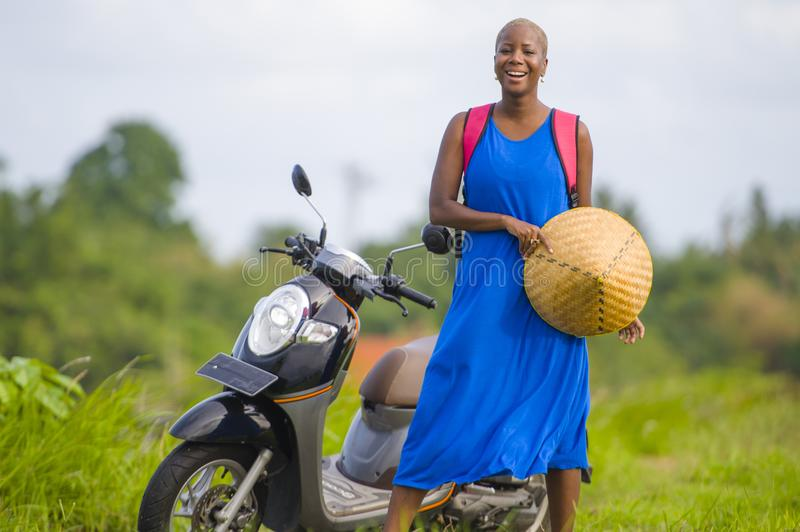 Young beautiful and happy tourist african american black woman looking around with scooter motorbike at green field tropical lands. Cape in adventure trip and stock photography