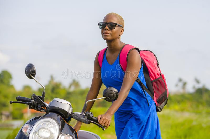 Young beautiful and happy tourist african american black woman looking around with scooter motorbike at tropical field. Young beautiful and happy tourist african royalty free stock photo