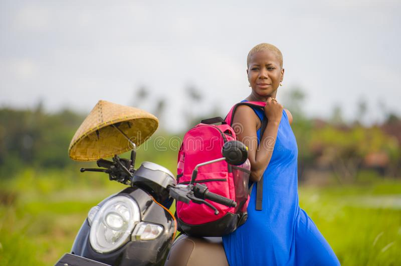 Young beautiful and happy tourist african american black woman looking around with scooter motorbike. At green field tropical landscape in adventure trip and royalty free stock image