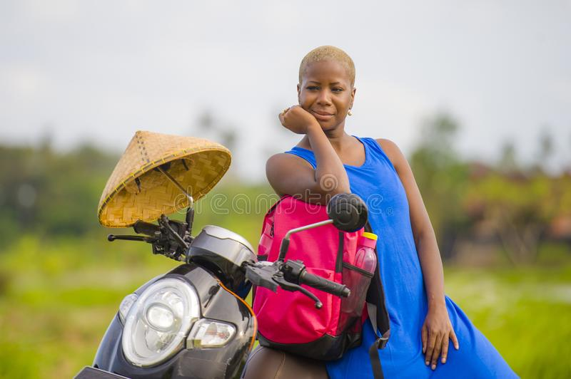 Young beautiful and happy tourist african american black woman looking around with scooter motorbike. At green field tropical landscape in adventure trip and royalty free stock photos