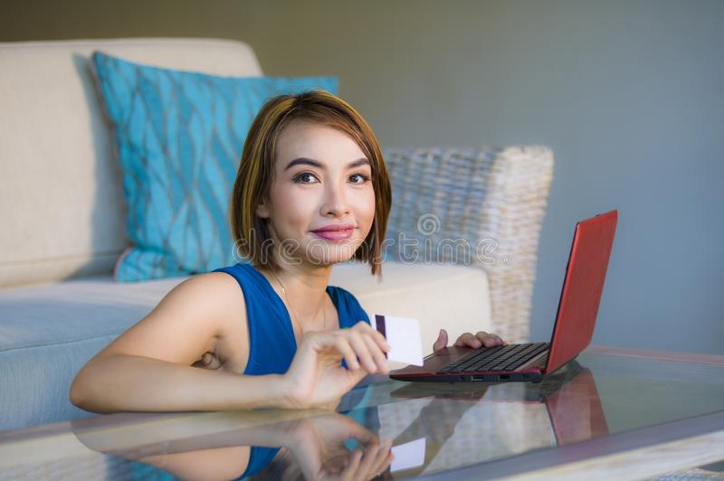 Young beautiful and happy woman at home living room holding credit card using laptop computer for banking and online shopping smil. Ing relaxed in e-business and stock image