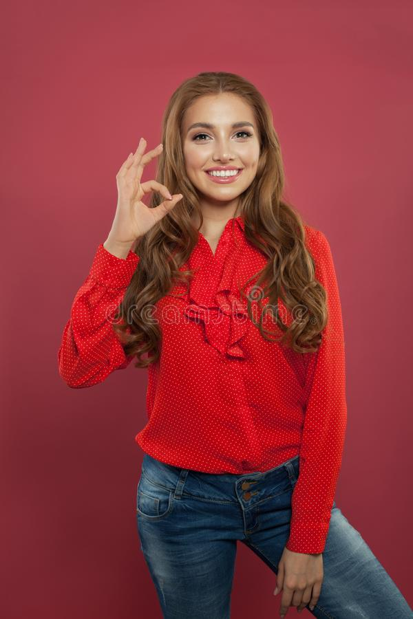Young beautiful happy woman showing ok sign on colorful pink background. Student girl with okay gesture, positive emotions stock photo