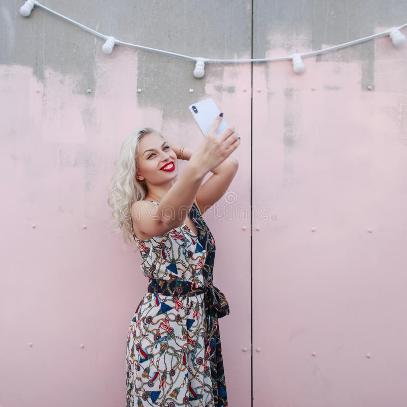 Young beautiful happy woman in a stylish dress makes selfie. On a smartphone near a pink wall on the street royalty free stock image