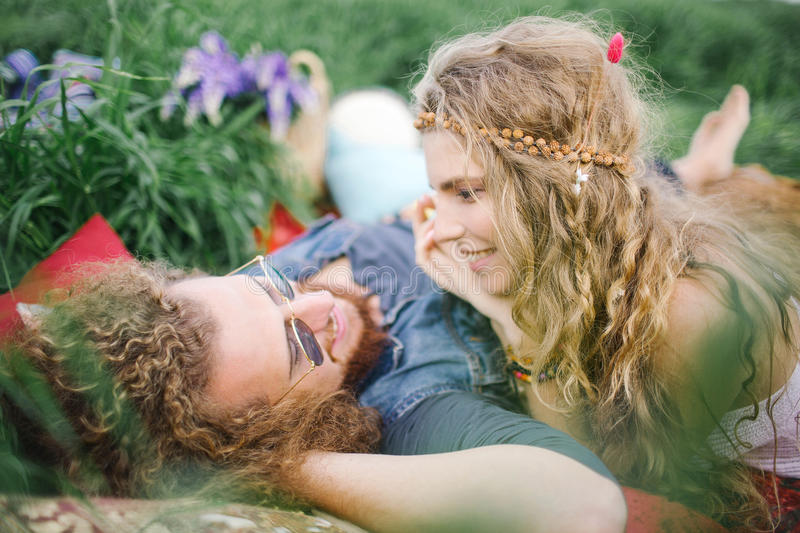 Young beautiful hippie couple lying on grass having fun stock images