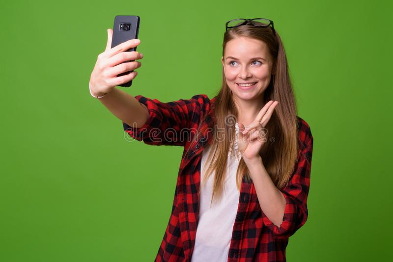 Young beautiful hipster woman with blond hair. Studio shot of young beautiful hipster woman with blond hair against green background royalty free stock image