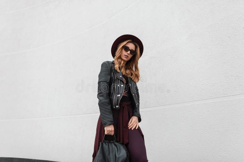 Young beautiful hipster woman in trendy sunglasses in a black jacket with a leather backpack in pants in an elegant hat. Is standing near a white wall outdoors royalty free stock image