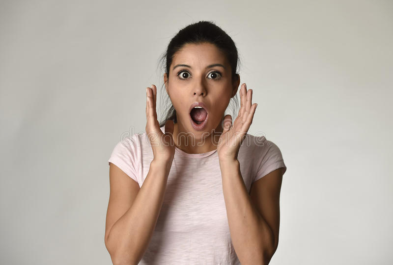 Young beautiful hispanic surprised woman amazed in shock and surprise with mouth big opened stock image