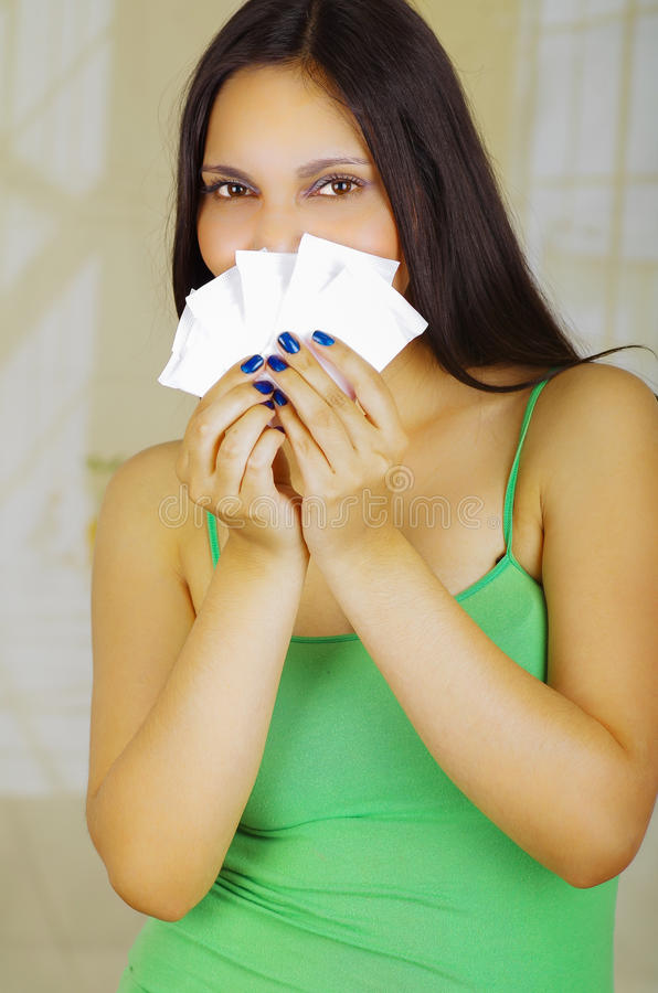 Young beautiful hispanic woman convering her nose and mouth with tampons using her both hands stock photography