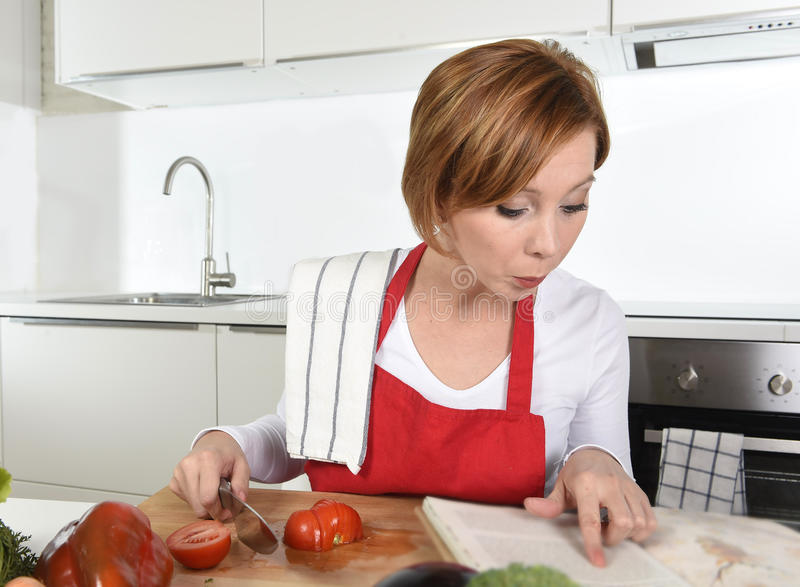 Young beautiful home cook woman in red apron at domestic kitchen reading cookbook following recipe holding knife. Slicing tomato in housework healthy eating and royalty free stock image
