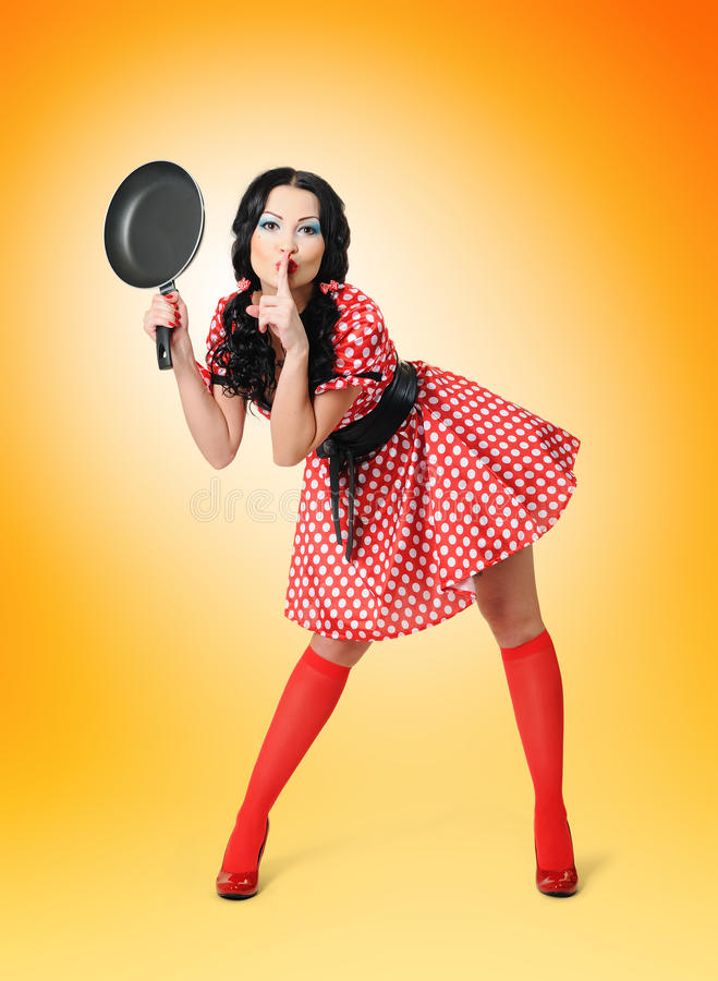 Young beautiful housewife with frying pan