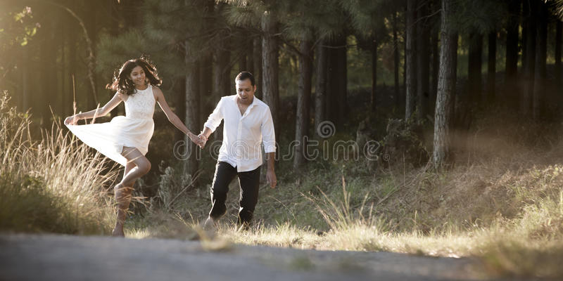 Young beautiful Indian couple dancing playfully in field stock image