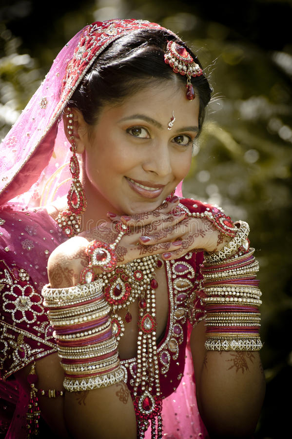 Young beautiful Indian Hindu bride sitting in garden outdoors. With face resting on hands royalty free stock images