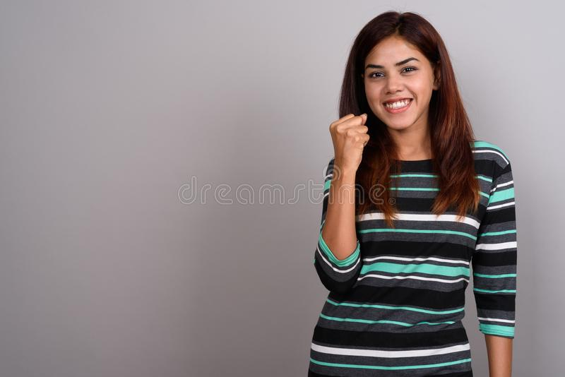 Young beautiful Indian woman against gray background royalty free stock photography