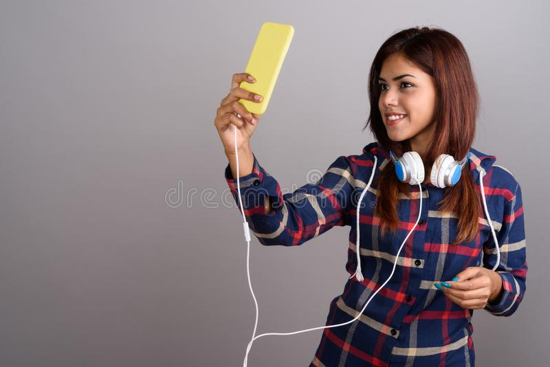 Young beautiful Indian woman wearing headphones and using mobile stock photo