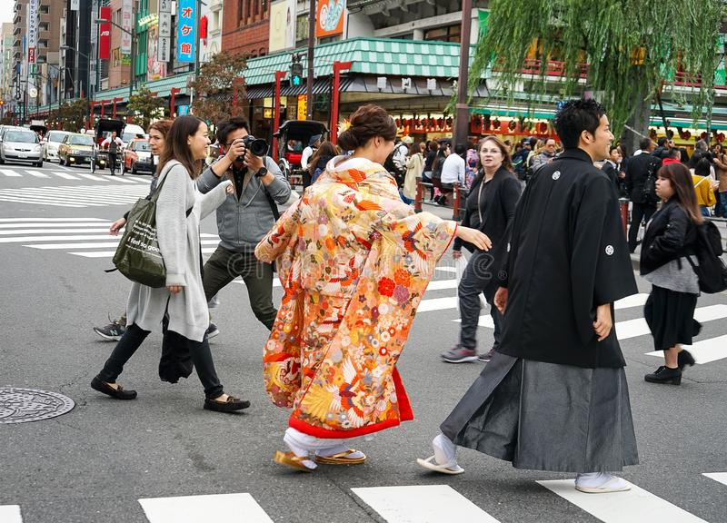 Young beautiful Japanese couple dressed in national Japanese costumes and photographed on street city Tokyo, Japan stock images