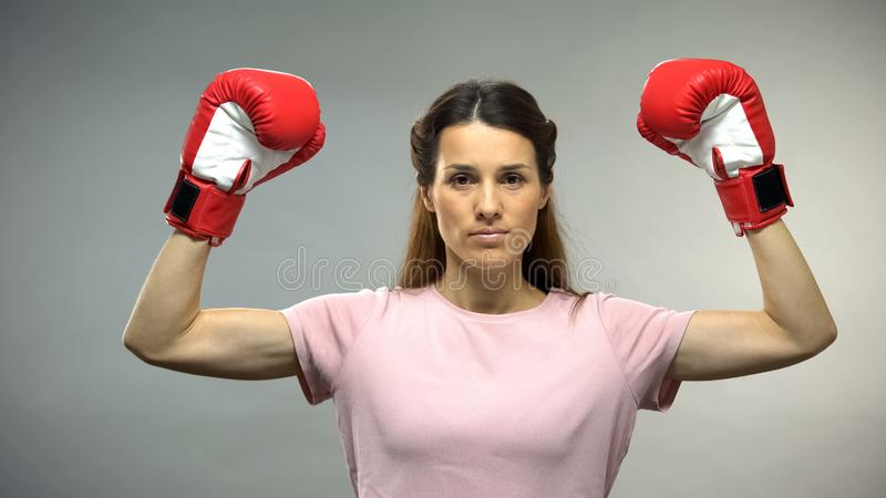 Young beautiful lady in boxing gloves raising hands up, cancer survivor, concept stock photography