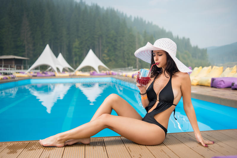 Young beautiful lady in a hat and black bikini sitting next to swimming pool and drinking cocktail royalty free stock images