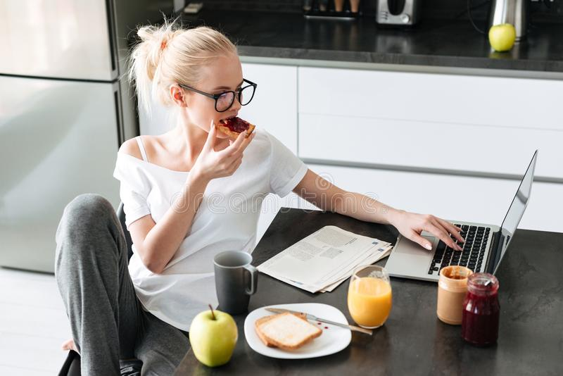 Young beautiful lady have breakfast and using laptop computer in kitchen royalty free stock photo